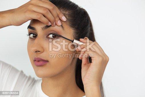 istock Young Indian Woman Applying Mascara on Eyelashes 639106534