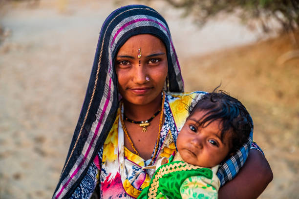 Young Indian woman holding her baby, desert village, India Young Indian woman with her baby. Thar Desert, Rajasthan, India. developing countries stock pictures, royalty-free photos & images