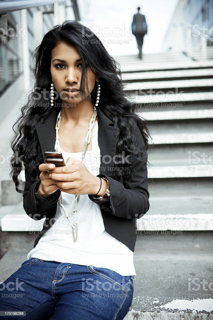 Young Indian Woman sitting on staircase with mobile phone stock photo