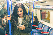 Young indian woman looking at her smart phone and typing while travelling on the tube in London. She is standing and holding with an hand. Transport and commuting concepts. Colours filter added.