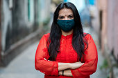 Young Indian woman wearing pollution mask against Pollution, Coronavirus or COVID-19. protection against covid 19 or coronavirus pandemic in outdoor location with extra copy space.