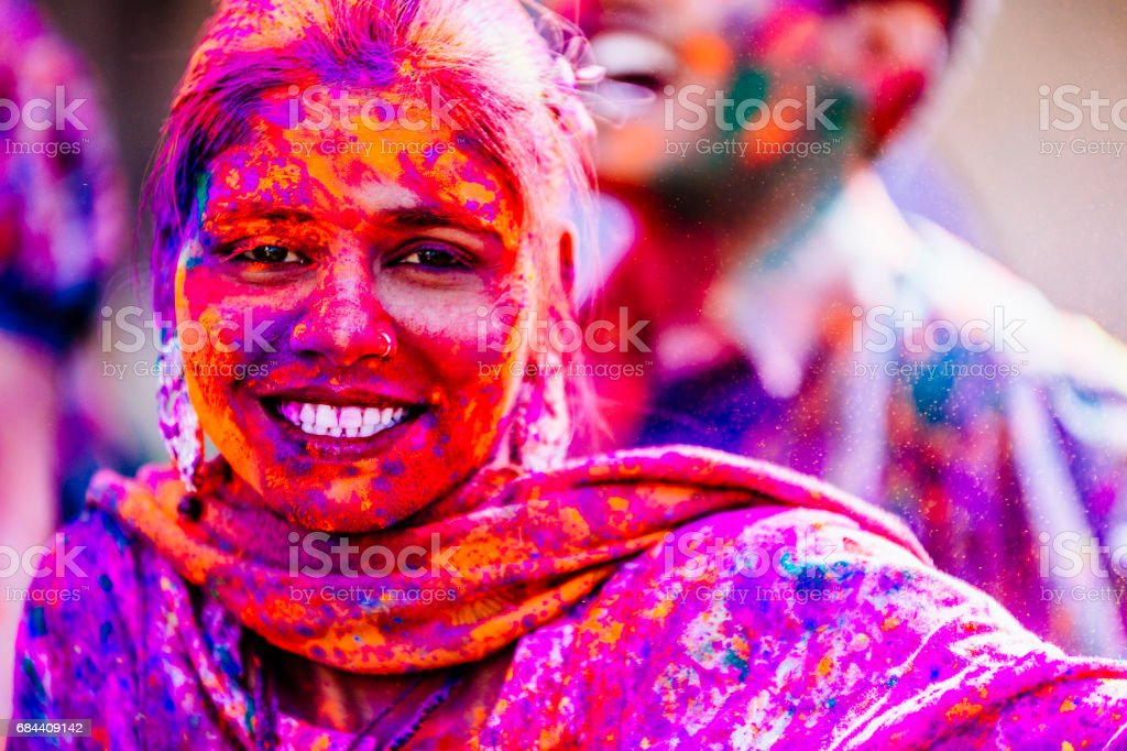 Young Indian woman, with her colorful face and clothes, dancing with her friends during the Holi Festival celebration in Jaipur India. stock photo