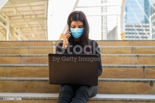 Portrait of young Indian woman with mask for protection from corona virus outbreak at skywalk bridge in the city outdoors