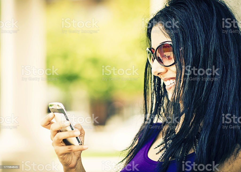 Young Indian Woman Writing Text on Mobile Phone royalty-free stock photo