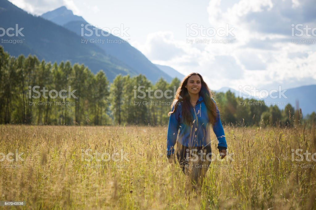Young indigenous Canadian woman walking in a field stock photo