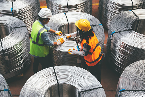 Aerial view of young engineer man and industrial worker woman checking production line and testing quality of steel pipe coils at warehouse section in cable factory. XXXL