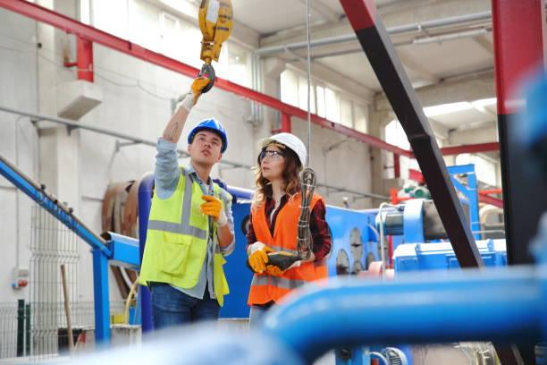Junge Industrie-Mitarbeiter halten und arbeiten mit Fernbedienung für den Betrieb von Kranen – Foto