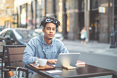 Young influencer is blogging from a sidewalk caffee