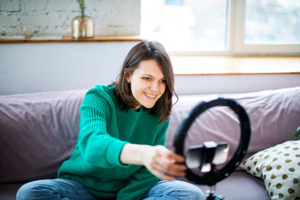 Young influencer woman streaming live video with smartphone and led stock photo