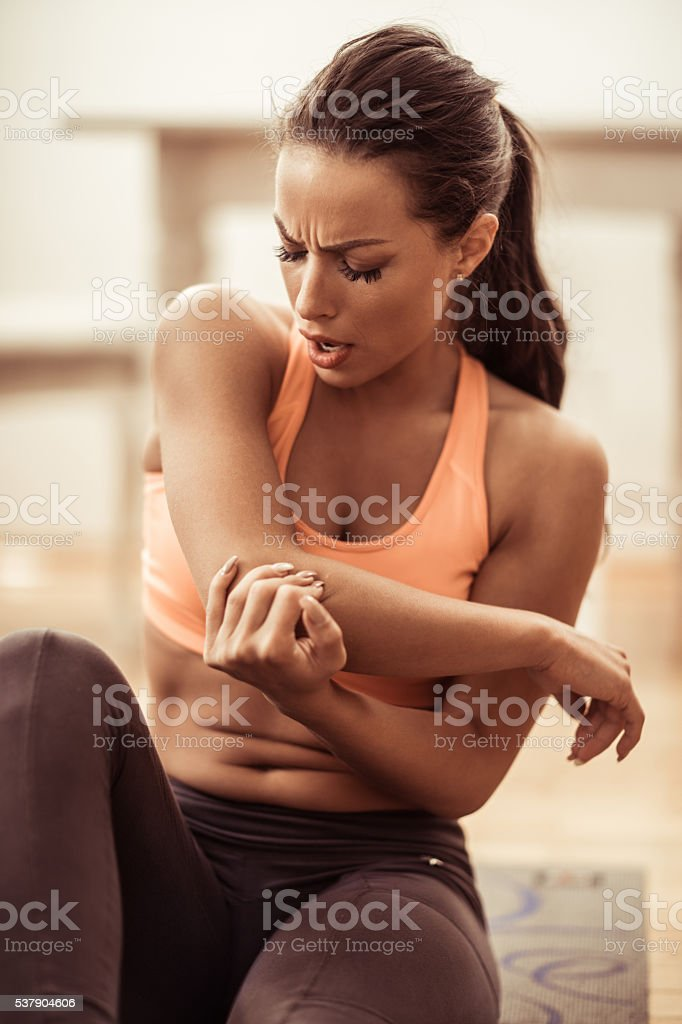 Young injured athletic woman holding her elbow in pain. stock photo