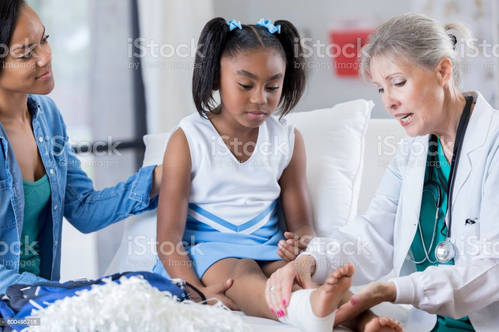Young injured cheerleader in the emergency room stock photo