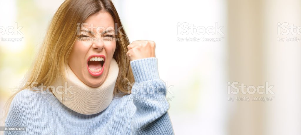 Young injured woman wearing neck brace collar irritated and angry...