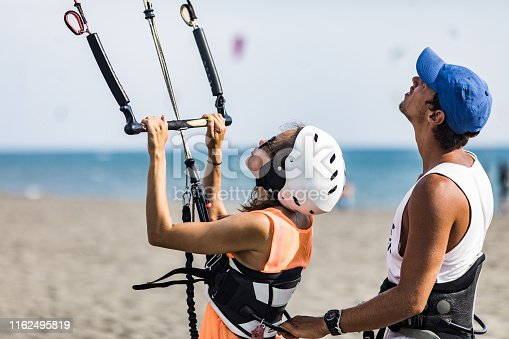 Young male instructor showing a woman the basis of kitesurfing on the beach.
