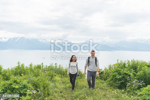 Young interracial couple hiking to a beautiful mountainous viewpoint in Alaska