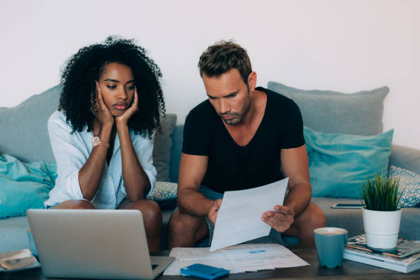 "Young interracial couple in the couch stressed with financial problems doing calculations with paper work""n Young interracial couple in the couch stressed with financial problems doing calculations with paper work""n debt ceiling stock pictures, royalty-free photos & images"
