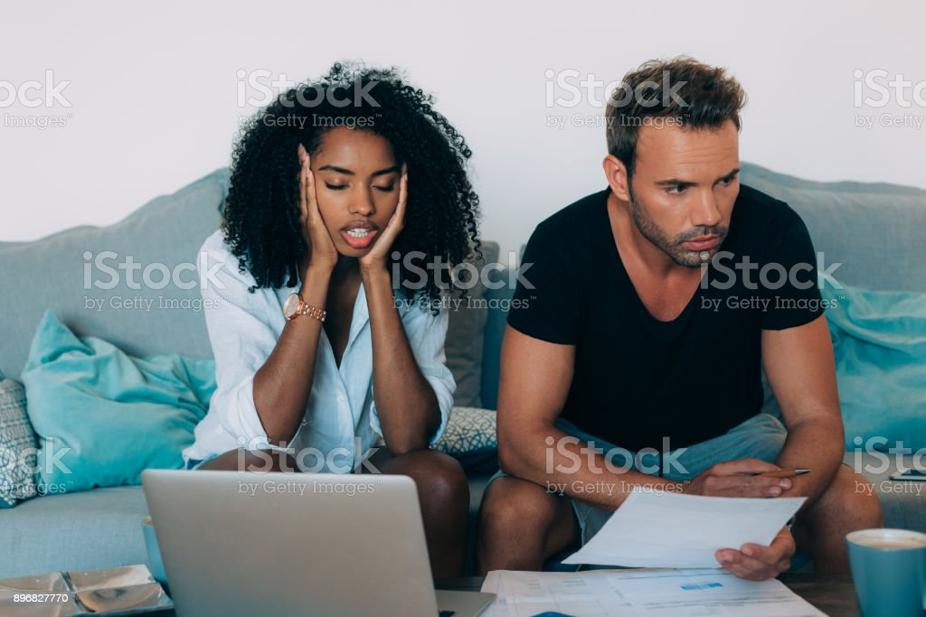 Young interracial couple in the couch stressed with financial problems doing calculations with paper work'n stock photo