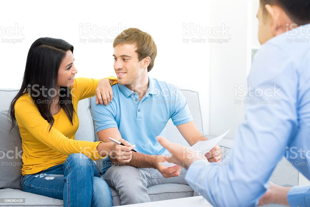 Young interracial couple meeting with consultant at home stock photo
