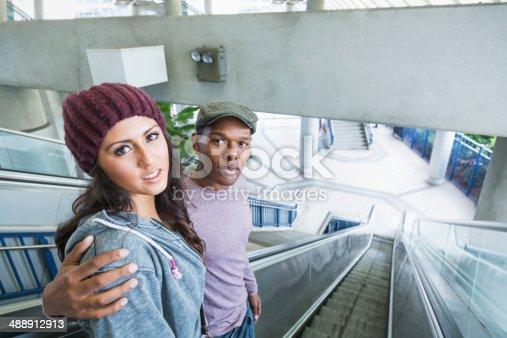 521022435 istock photo Young interracial couple on escalator 488912913