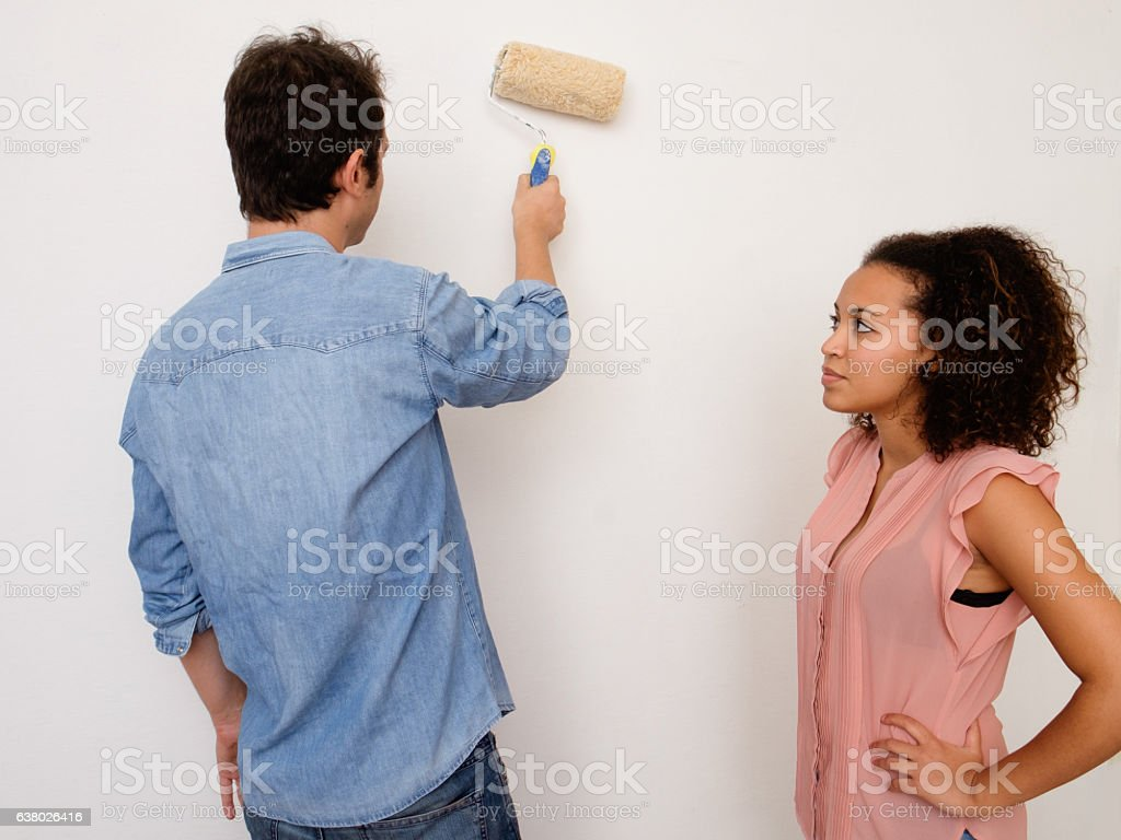 Young interracial couple painting the house wall together - foto stock