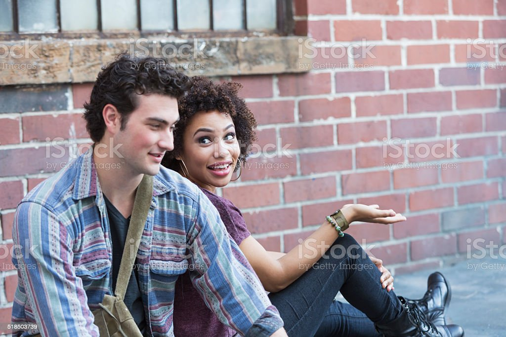Young interracial couple sitting and talking stock photo