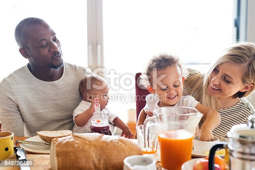 istock Young interracial family with little children having breakfast. 849736486