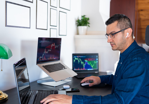 Young investor man is analyzing stock market with charts on laptop computer screen at home office. Stock Exchange, investment, cryptocurrencies and financial trading with online business.