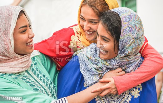 istock Young islamic friends having fun outdoor - Happy arabian friends laughing and smiling together - Friendship, religion, ethnic culture and youth concept - Focus on top girl face 1131765582
