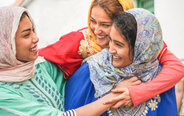 young islamic friends having fun outdoor - happy arabian friends laughing and smiling together - friendship, religion, ethnic culture and youth concept - focus on top girl face - pakistan foto e immagini stock