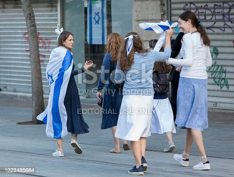 Jerusalem, Israel, May 8, 2019: Young israeli jewish teenagers, girls going with Israeli flag at Independence Day, in Jerusalem, Israel