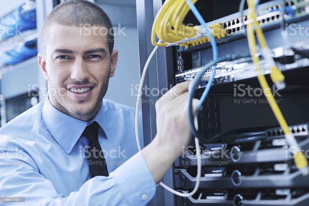 A young IT engineer in a data center server room  royalty-free stock photo