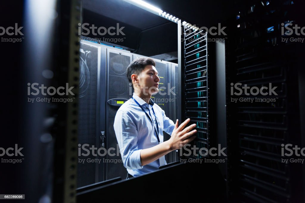 Young IT engineer inspecting data center servers - Royalty-free Administrator Stock Photo