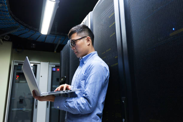Young IT engineer inspecting data center servers stock photo