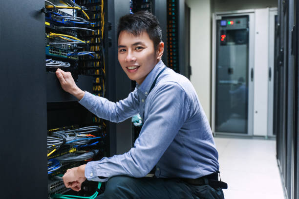 Young IT engineer near data center servers stock photo
