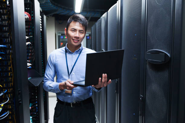 Young IT engineer standing near data center servers stock photo