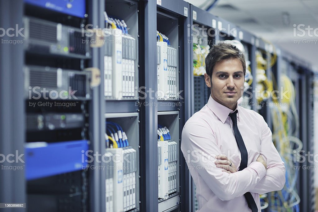 Young IT engineer standing near datacenter servers stock photo