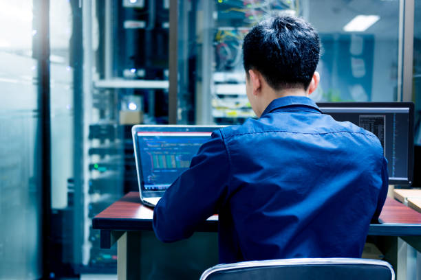 young it engineer working at server room is multi display, data protection security privacy concept. - hacker stock photos and pictures