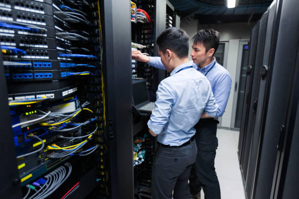 Young IT engineers inspecting data center servers stock photo
