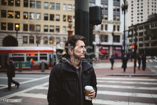 Young man working in the vibrant Silicon Valley IT scene standing on the sidewalk in San Francisco, downtown district, having a coffee break.