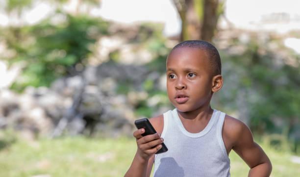 Jeune garçon jamaïcain avec un téléphone portable - Photo
