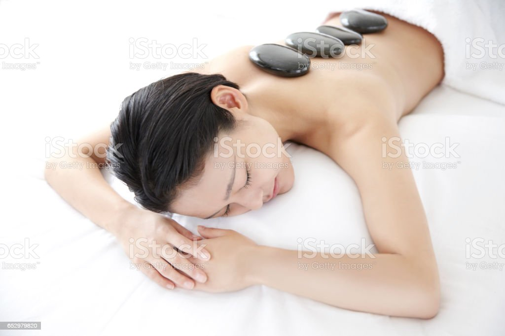 Young Japan woman receiving a hot stone therapy stock photo