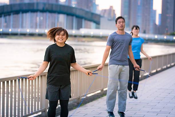 Young Japanese athletes jumping ropes along river stock photo