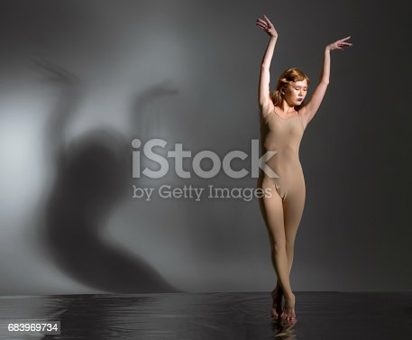 Beautiful young woman modern ballet dancer dressed in skin colored ballet leotard. She performs the ballet pose. The ballerina is standing tiptoe. Her hands are raised over head. Her eyes are closed. Shooting in studio on foil covered floor on gray background, the shadow of the dancer on wall
