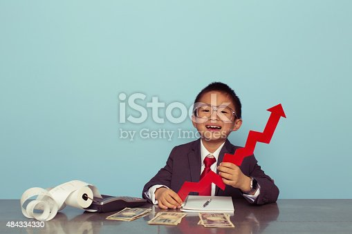 A young Japanese boy and businessman sits at his desk holding a line graph arrow showing his business is making money and growing. Boy dressed in business suit. Retro styled.