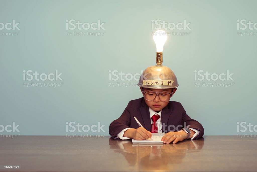 Young Japanese Business Boy Wearing Lit Up Thinking Cap stock photo