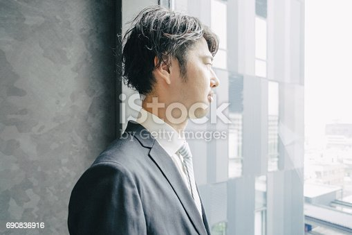 istock Young Japanese businessman looking out of office window 690836916
