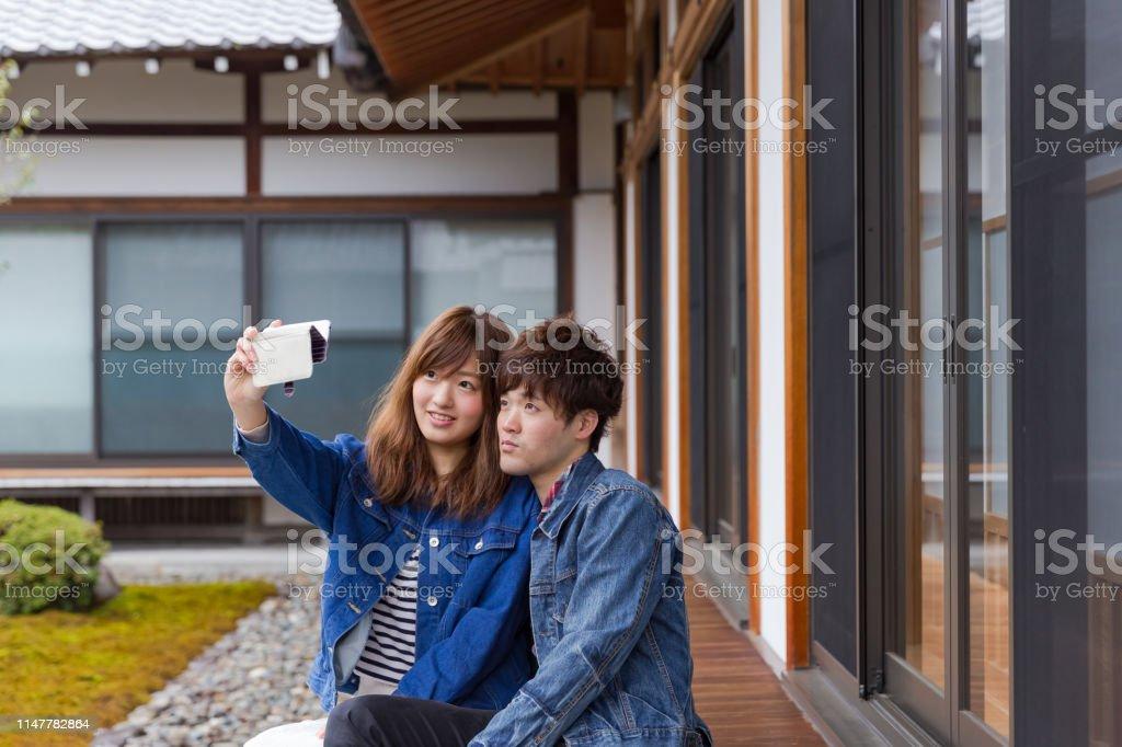若い日本のカップルは、スマートフォンで自分撮りを取ります ストックフォト