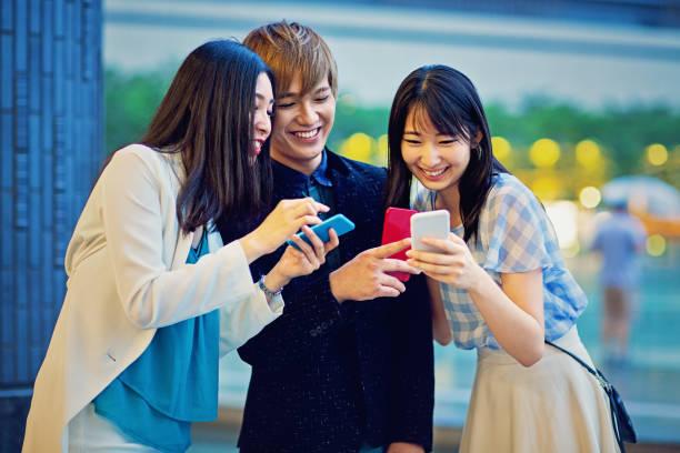 自分の携帯電話に若い日本人の友達を探し ストックフォト