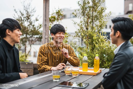 Men in early 20s sitting at picnic table on Tokyo rooftop laughing as they enjoy bottled tea and conversation.
