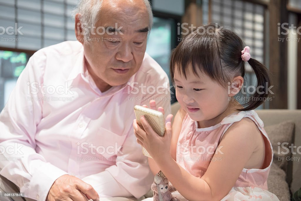 Young Japanese girl and grandfather playing with handheld device stock photo
