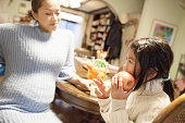 istock young Japanese girl eating apple with her pregnant mother 629277346